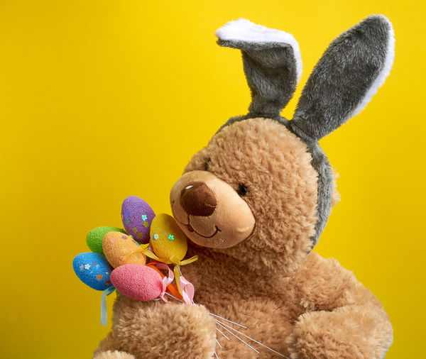 Close-up of stuffed toy against yellow background