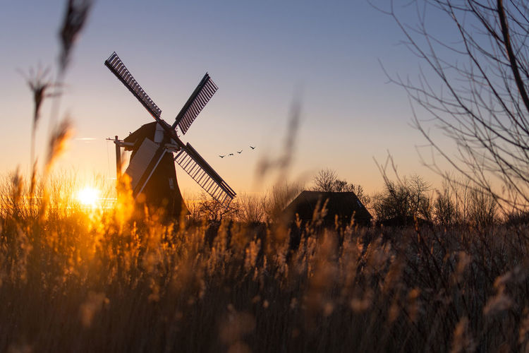 Traditional windmill on field against sky at sunset