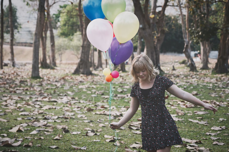 Young woman holding balloons while standing on field