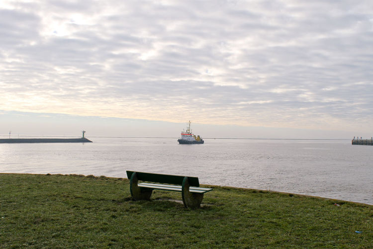 Empty bench on field against seascape