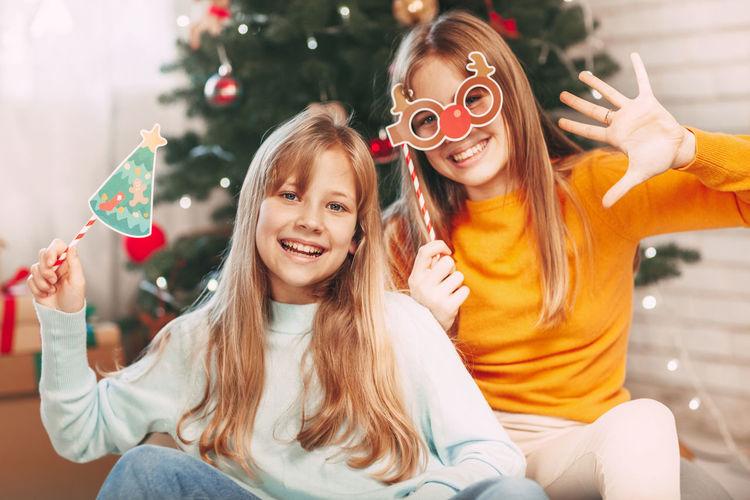 Portrait of happy friends sitting on christmas tree