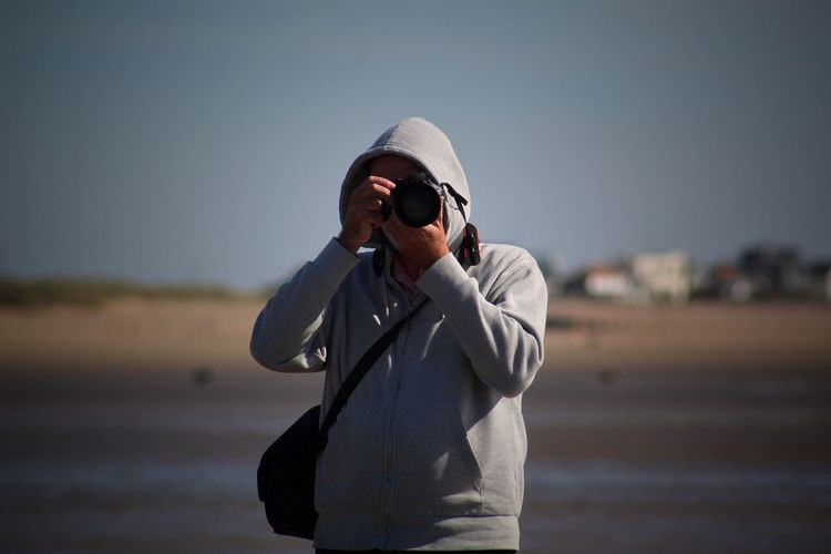 Man photographing with camera at beach against sky