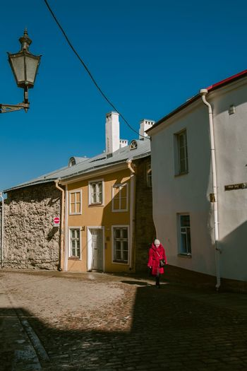 Primary colours in Tallinn's old town Street Portrait Real People Street Photography Light And Shadow Architecture And People Architecture Built Structure Building Exterior Sky Building Nature Clear Sky Residential District House Blue Sunlight City Street Outdoors