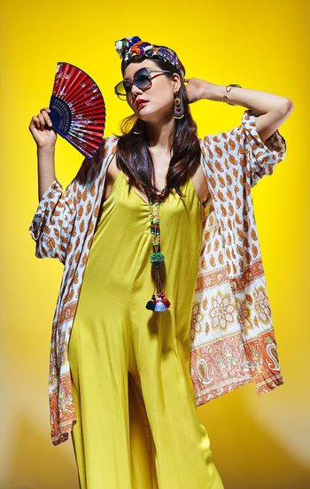 Young woman with umbrella standing against yellow background