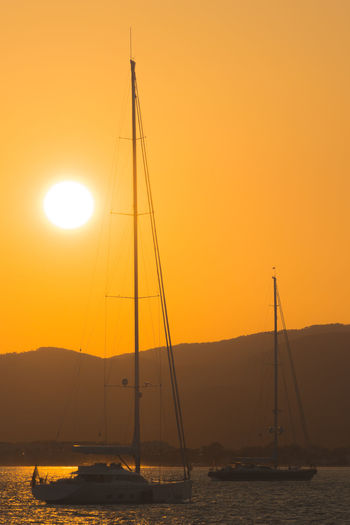 Silhouette Sailboats In Sea Against Orange Sky