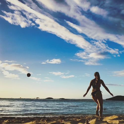 Woman In Bikini Playing With Ball At Beach Against Blue Sky