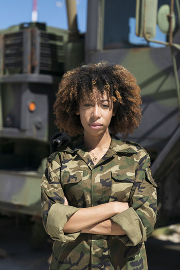 Portrait of woman standing against car
