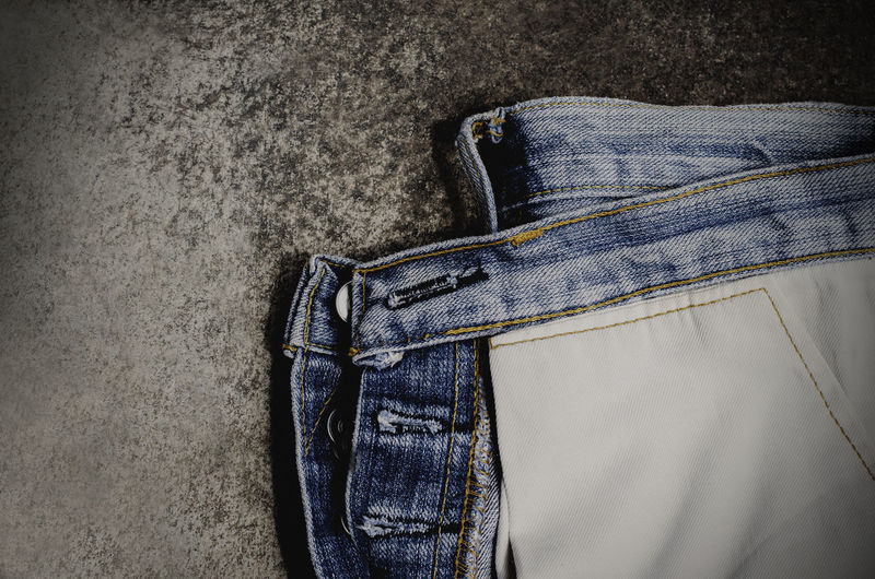 Old Fashioned Jeans on Cement Space Backgrounds Blue Casual Clothing Close-up Clothing Denim Fashion High Angle View Indoors  Jacket Jeans Lifestyles Midsection Pocket  Still Life Textile Textured