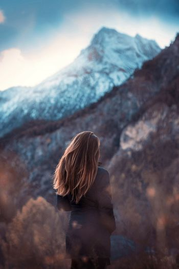 Rear view of woman standing against mountains