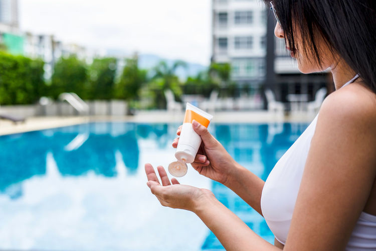 Midsection of woman holding suntan lotion at poolside