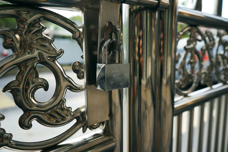 Chrome lock hanging on the stainless steel fence