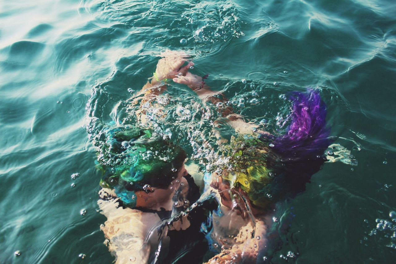 High angle view of friends with dyed hair swimming undersea