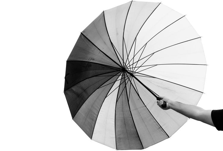 Person holding umbrella against white background