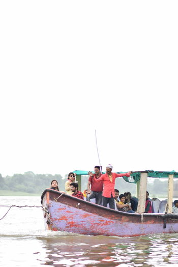 People sitting on boat against clear sky