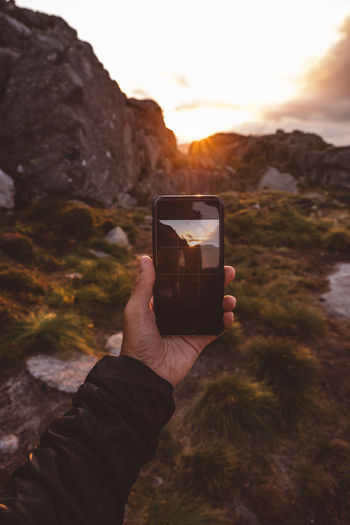 Midsection of person photographing through smart phone against sunset sky