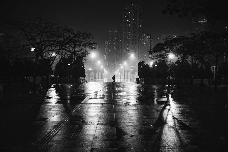Illuminated street lights on wet footpath at night