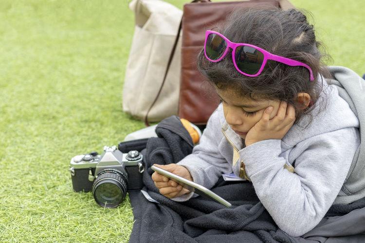 Cute Girl Using Phone On Grassy Field