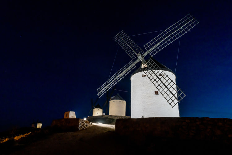 Traditional windmill against clear sky at night