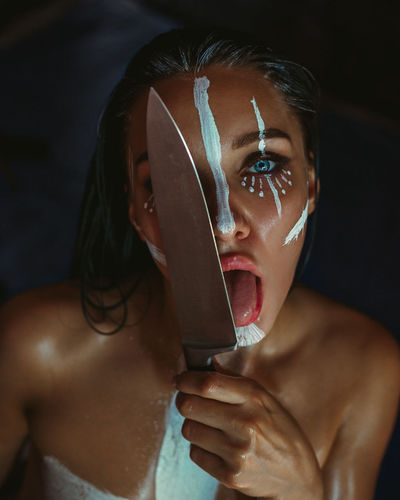 Close-up portrait of young woman holding kitchen knife