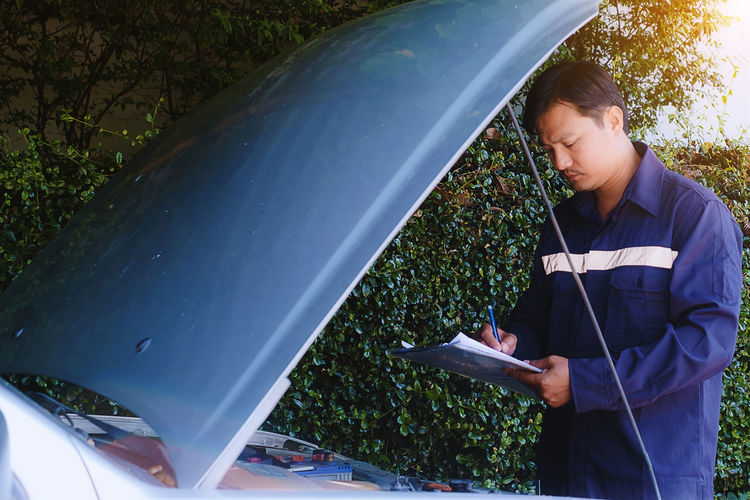 Mechanic writing in notepad by car against plants
