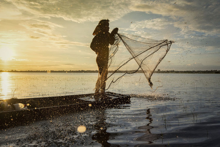 Side view of man throwing net in river