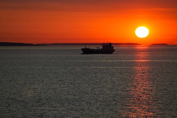 Boat sailing in sea against orange sky