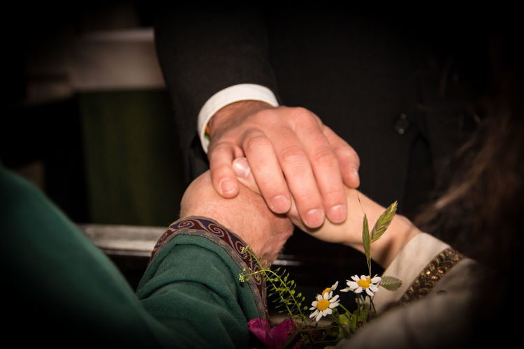 Cropped Image Of Priest Holding Bride And Groom Hands During Wedding Ceremony