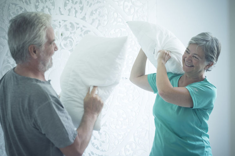 Cheerful senior couple pillow fighting at home