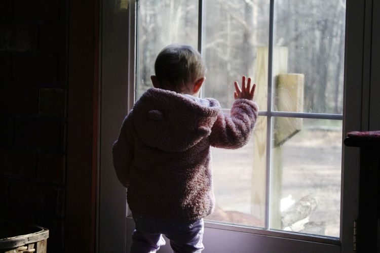 Rear view of baby girl at window