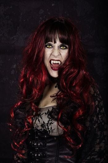 Portrait Of Woman With Long Hair Wearing Costume During Halloween Against Black Background