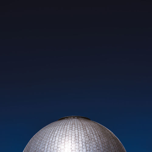 Low angle view of building dome against clear blue sky