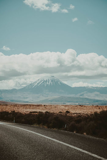 Scenig drive through Rangipo Desert with view of Mount Ngauruhoe. Mountain Sky Road Scenics - Nature Beauty In Nature Landscape Day Snowcapped Mountain Nature Mountain Range Mountain Peak Outdoors No People Mount Ngauruhoe Ngauruhoe Mount Doom Lord Of The Rings Volcano Volcanic Landscape Desert