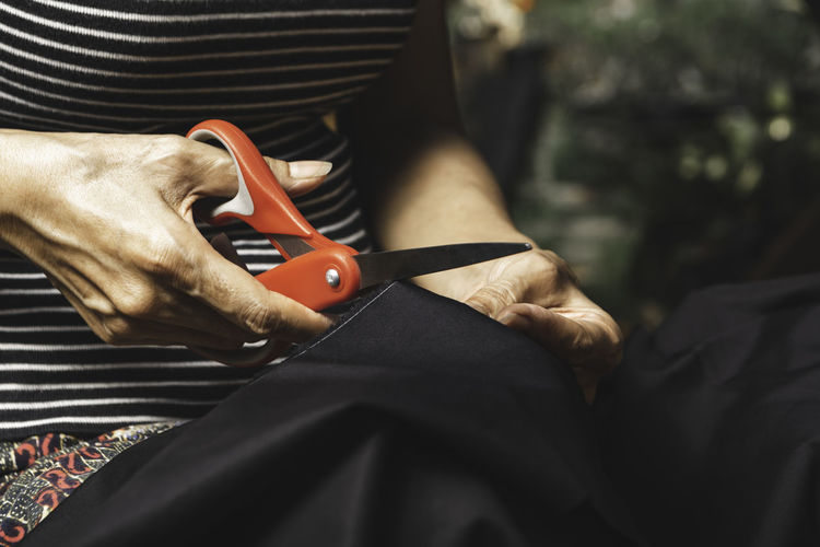 Midsection of woman cutting fabric