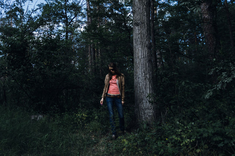 The Alone Sad Woman Staying Near The Tree In the Gloomy Forest Tree Plant Forest Land One Person Casual Clothing Tree Trunk Standing Trunk Full Length Nature Real People Growth WoodLand Day Leisure Activity Lifestyles Young Adult Non-urban Scene Outdoors Jeans Hairstyle Sadness Glasses