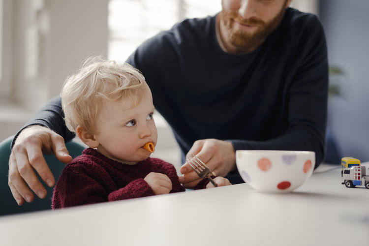 Father and son sitting on table