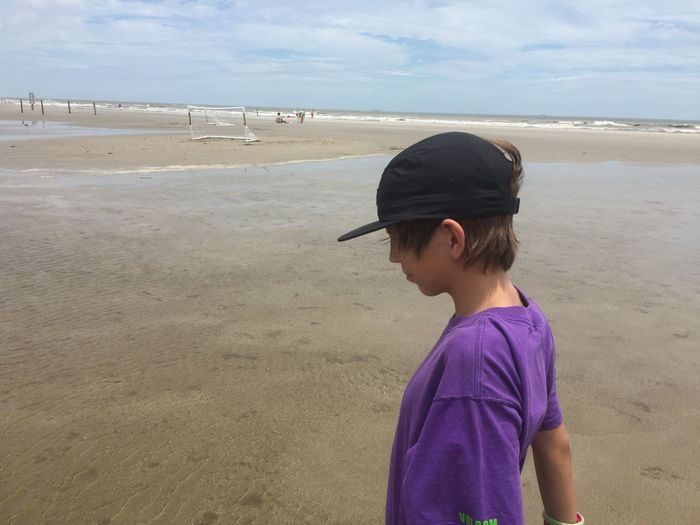 Side view of teenage boy wearing cap standing at beach against sky during sunny day
