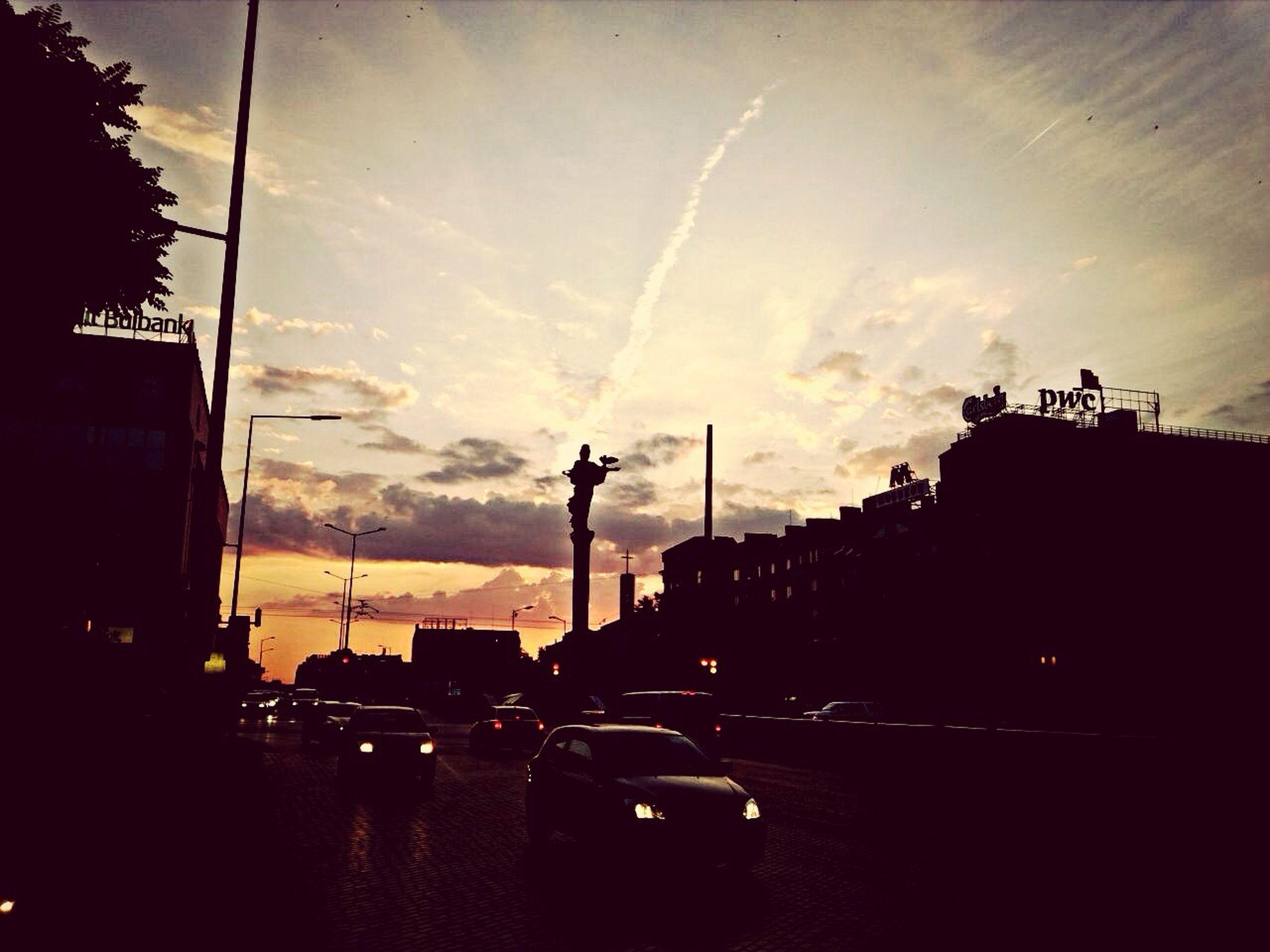 transportation, silhouette, sunset, building exterior, sky, mode of transport, built structure, architecture, land vehicle, car, street, cloud - sky, city, street light, dusk, road, illuminated, outdoors, cloud, building