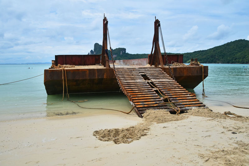 Old rusty corroded cargo barge in the bay ofPhi Phi Don island Ark Barge Beach Cargo Corrosion Ferry Industrial Island Landscape Landscapes With WhiteWall Load Old Phi Phi Ramp Rusty Sand Sea Seashore Ship Spotted In Thailand The Mix Up