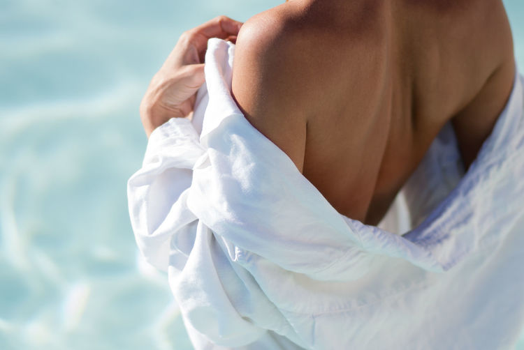 Rear view of woman with bathrobe in swimming pool
