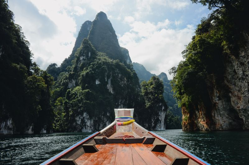 Boat in river with mountains in background against cloudy sky