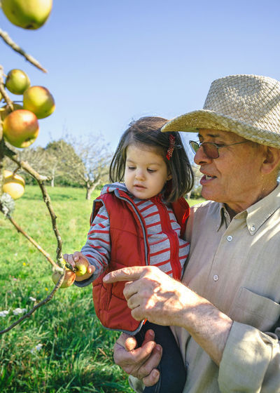 Grandfather With Granddaughter Standing By Apple Tree On Field