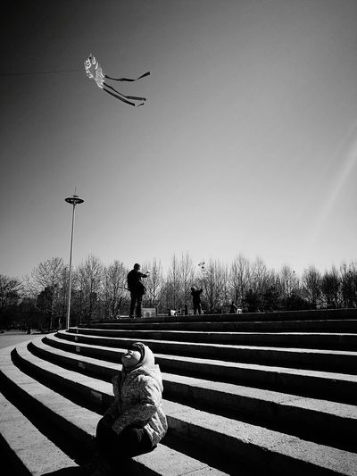 Girl looking at kite while sitting on steps against clear sky