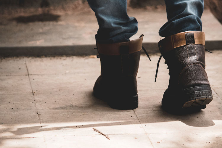 Body Part Boot Day Fashion Flooring Focus On Foreground Footpath High Angle View Human Body Part Human Foot Human Leg Human Limb Jeans Leather Leisure Activity Lifestyles Low Section One Person Outdoors Real People Shoe Standing Tiled Floor Unrecognizable Person Urban Fashion Jungle