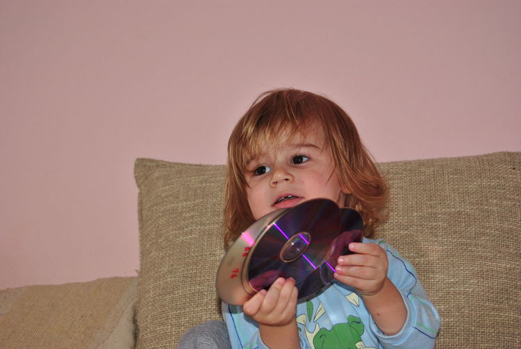 Close-up of boy holding compact discs while sitting on bed at home