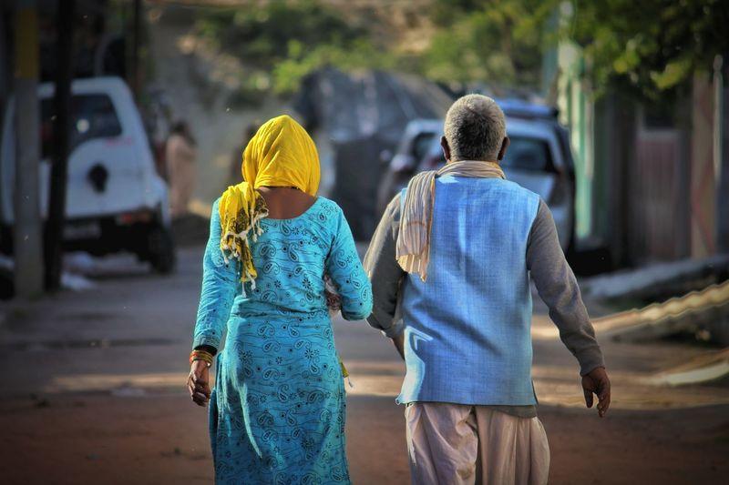 Rear view of people walking on road