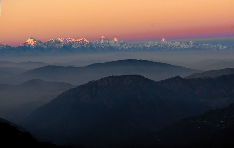 Scenic View Of Silhouettes Mountains Against Romantic Sky At Sunset