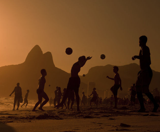 Silhouette friends playing soccer at beach against orange sky during sunset