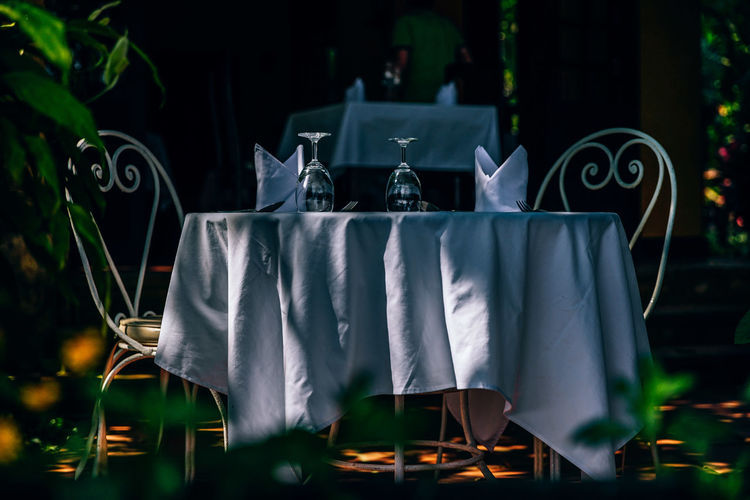 Close-up of chairs on table at night