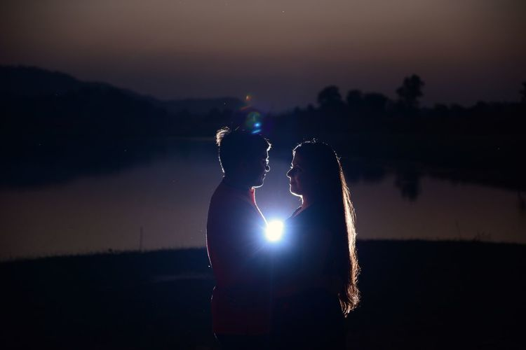 Flashlight Amidst Young Couple Standing Face To Face At Lakeshore Against Sky During Night