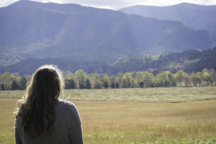 Rear view of woman on field against mountains